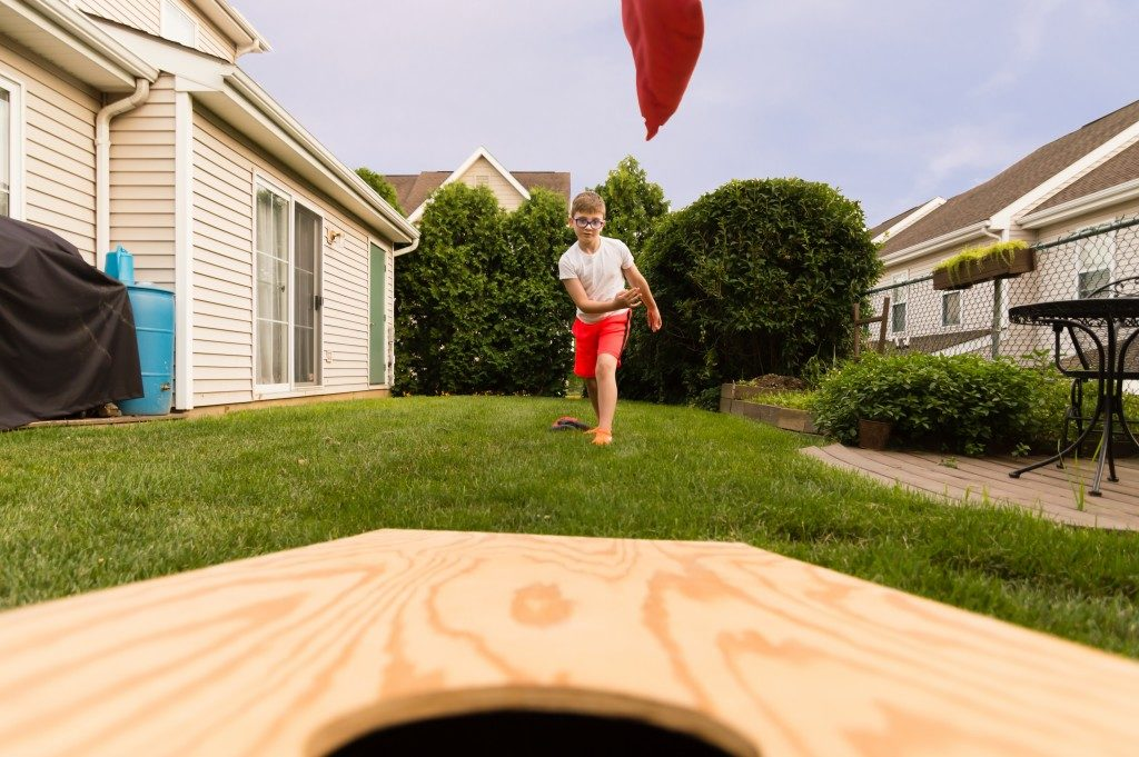 young kid playing cornhole