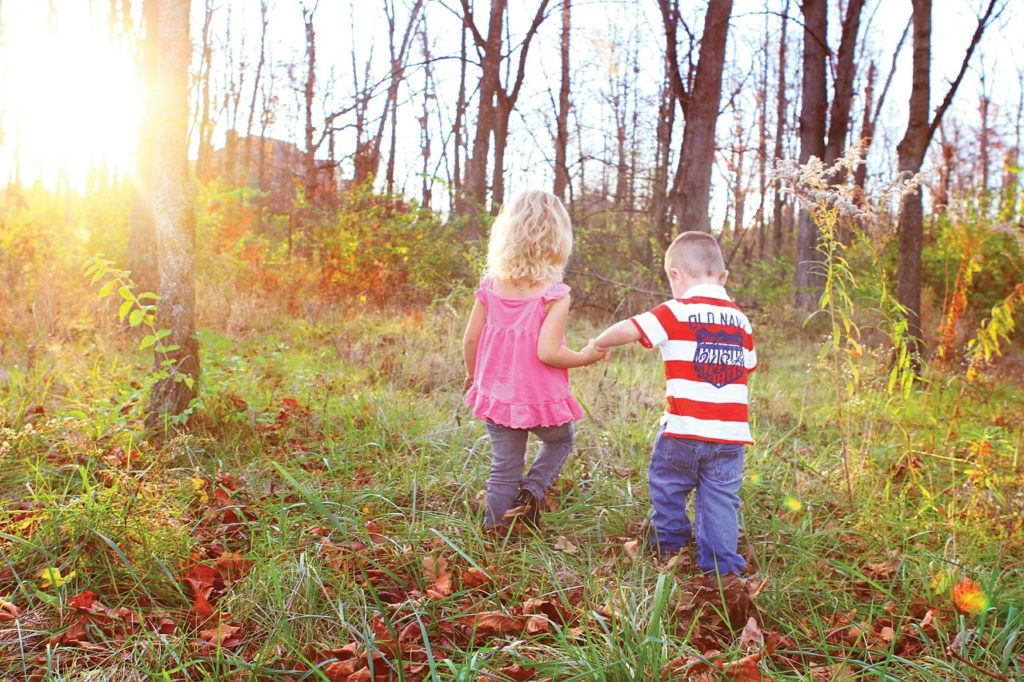 2 kids playing in the forest